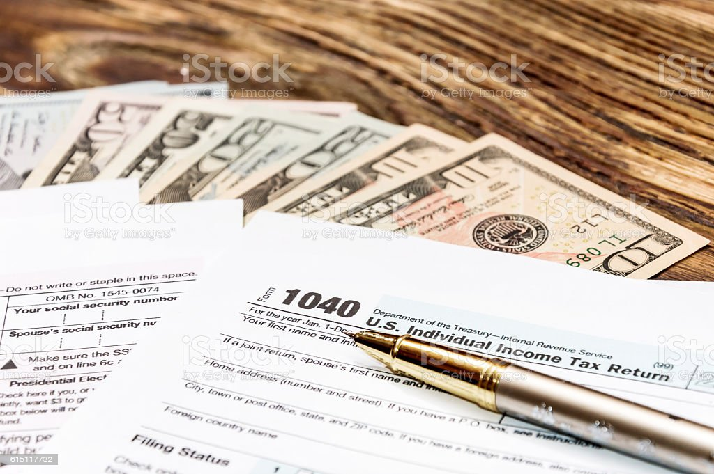 Tax form 1040 with pen and money on the table stock photo