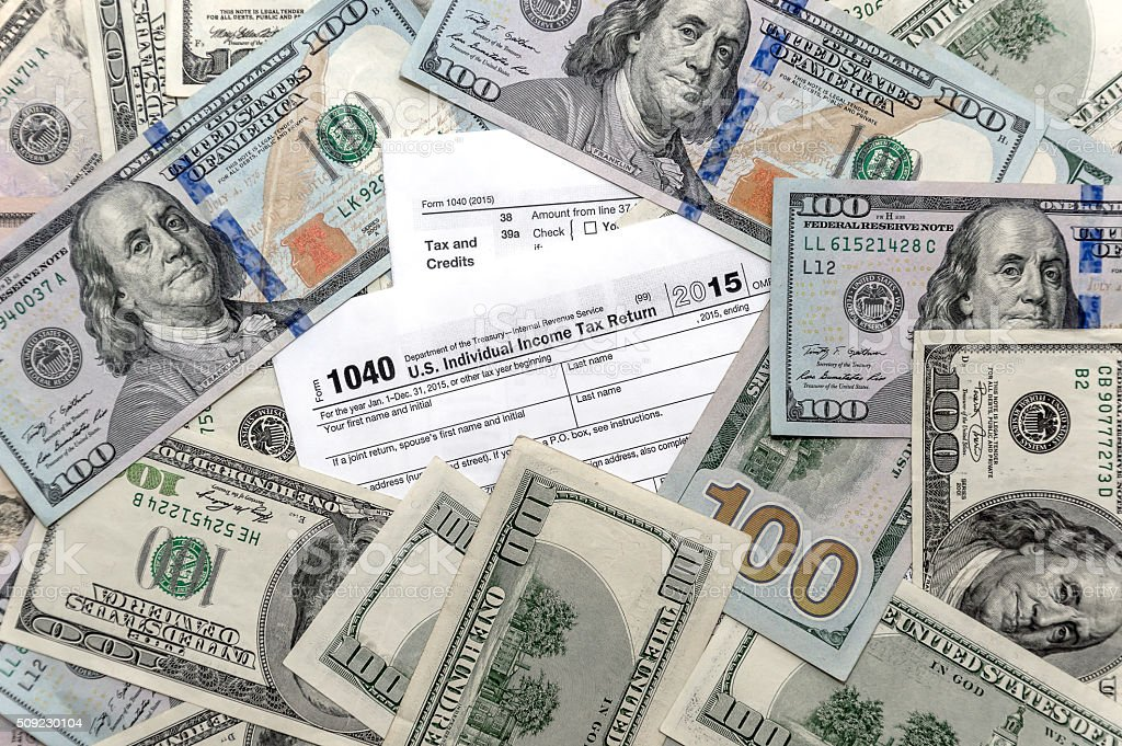 Tax form 1040 with US dollar bills stock photo