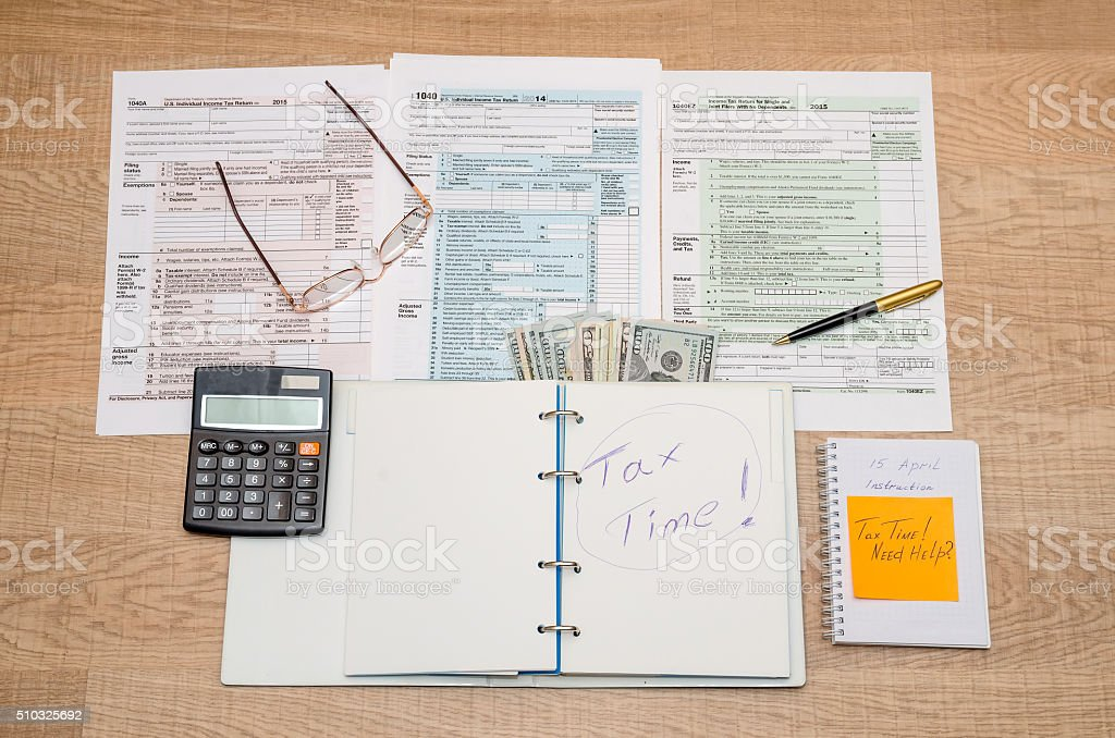 tax form, notepad, calculator and pen stock photo