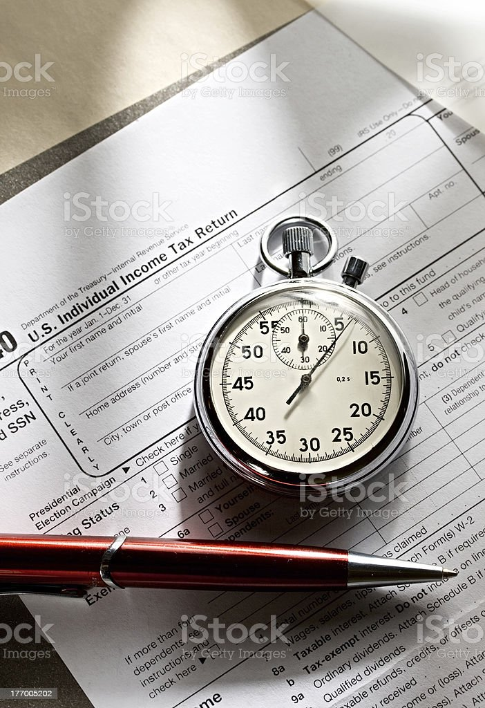 Tax form, red pen and stopwatch royalty-free stock photo