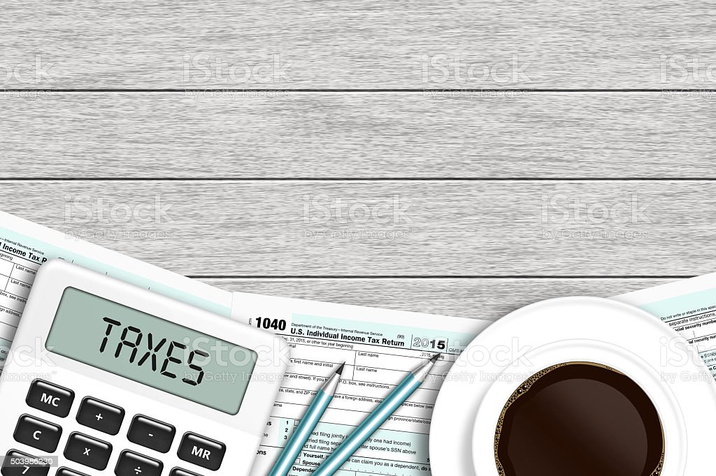 1040 tax form with calculator and coffee lying on desk stock photo