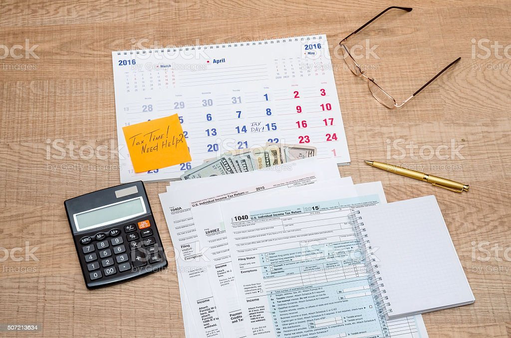 Tax form with calendar, pen, calculator, notepad and glasses stock photo