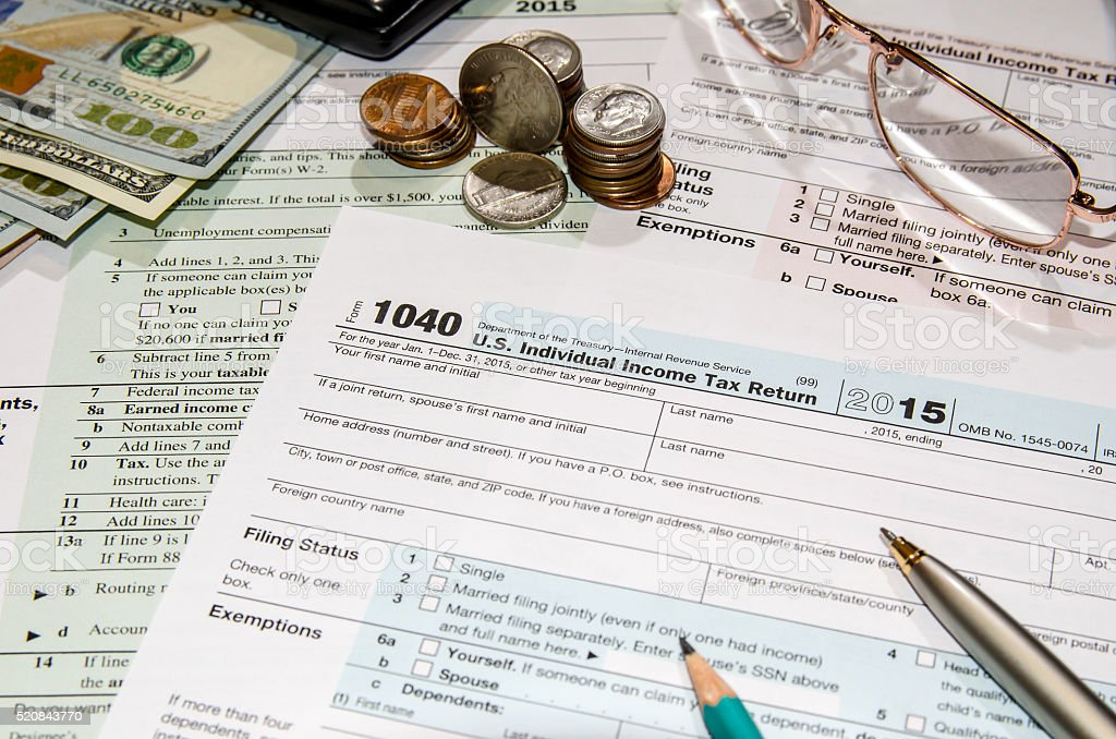 1040 tax form with dollar, glasses, mouse, calculator, notepad stock photo