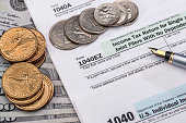 US tax form with dolllr bills and coins. taxation