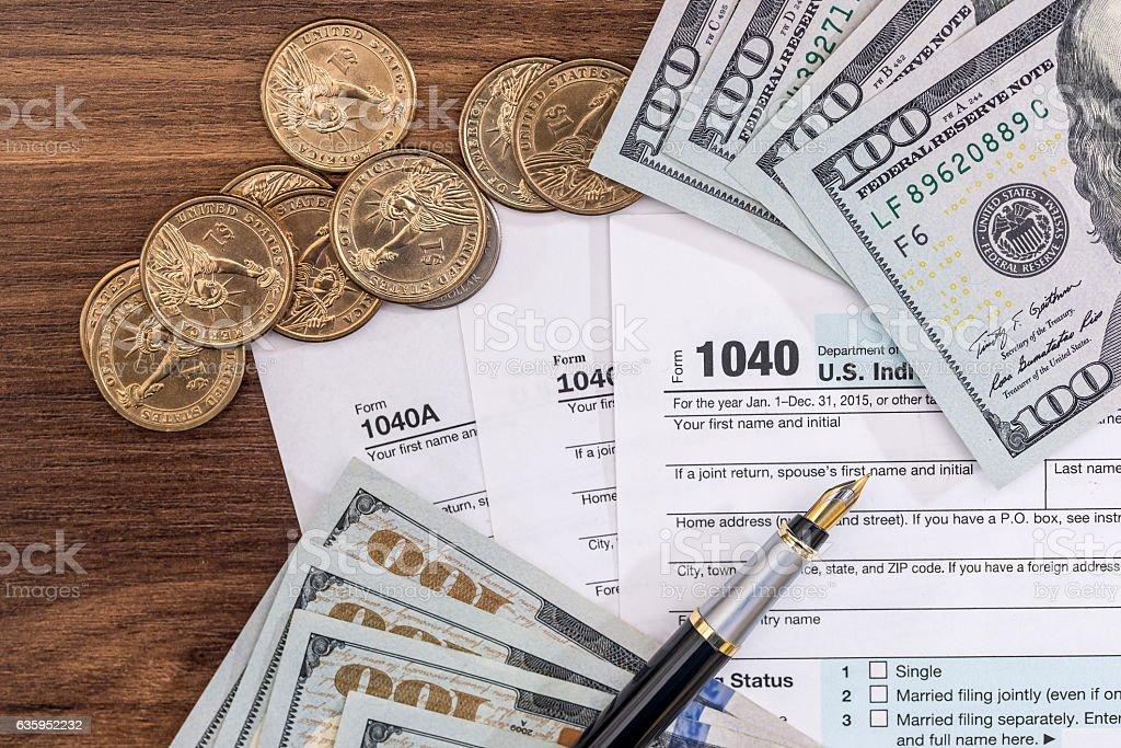 US tax form with dolllr bills and coins. taxation stock photo