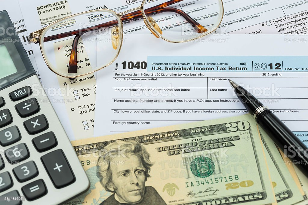 Tax form with pen, calculator, dollar banknote , and glasses tax stock photo