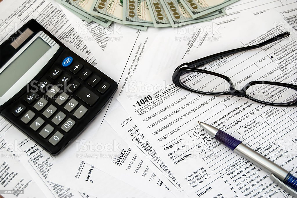 Tax form with pen, glasses, dollars and calculator stock photo