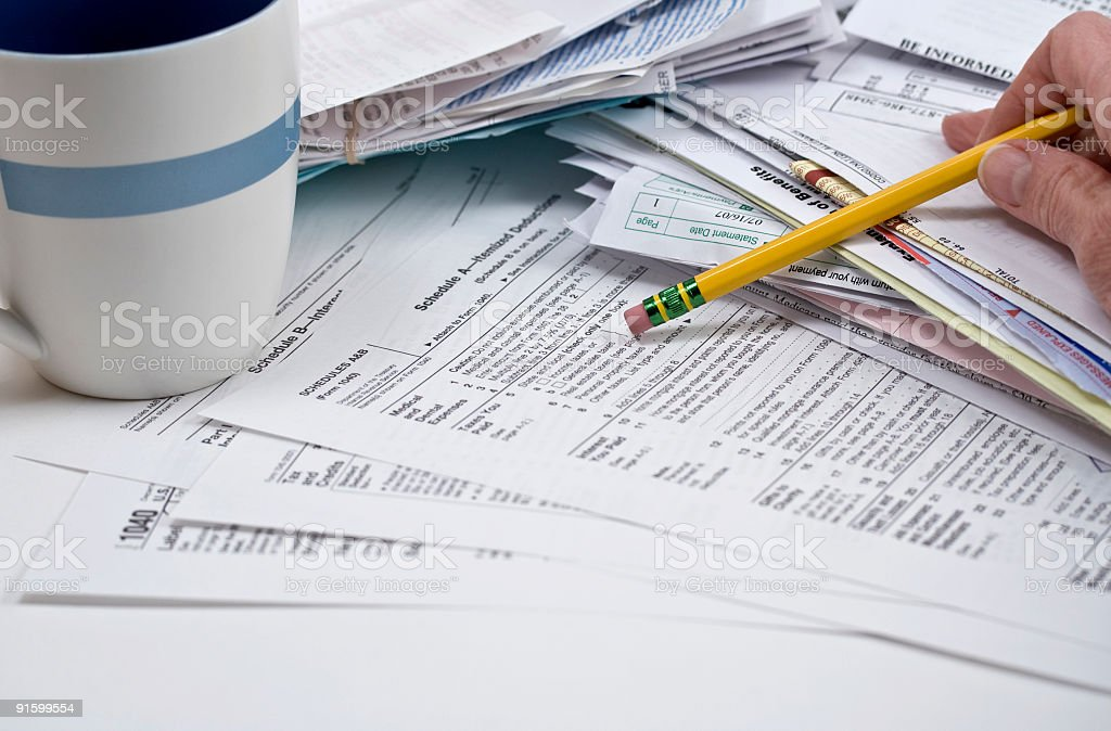 Tax Forms and cup with hand holding pencil royalty-free stock photo