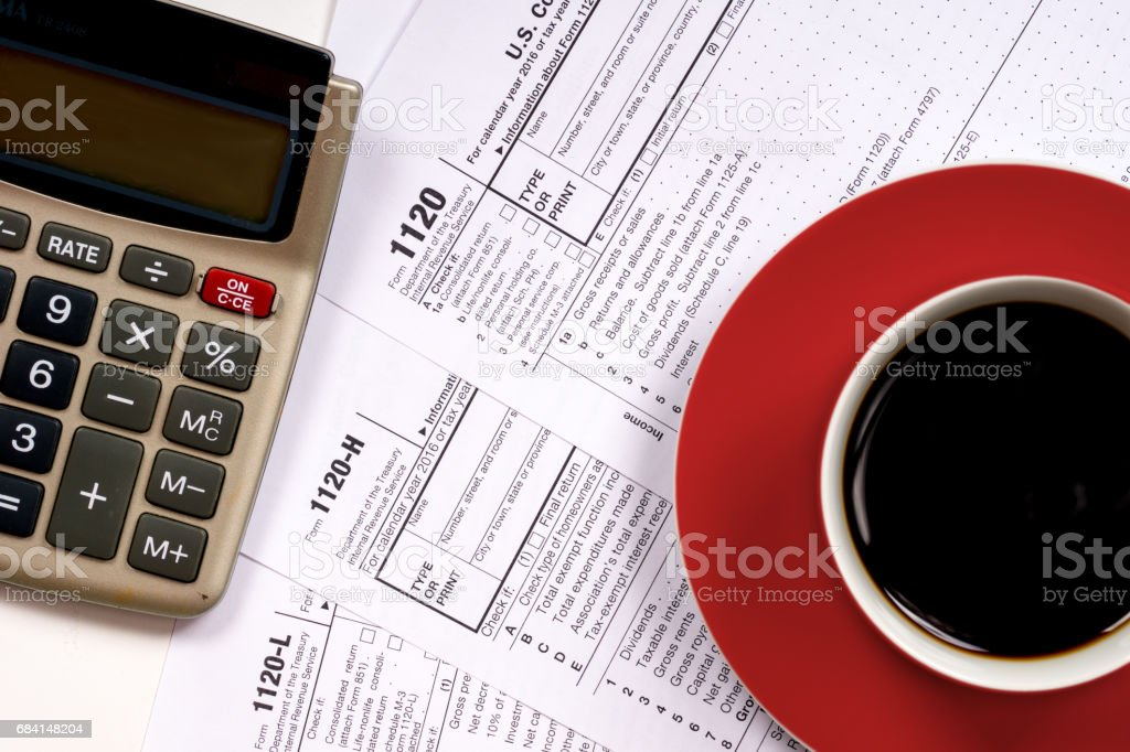 1120 tax forms top view with coffee cup and calculator stock photo