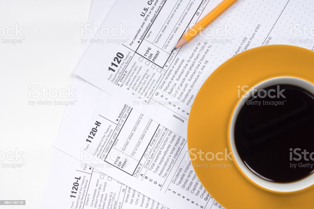 1120 tax forms top view with coffee cup and pencil stock photo