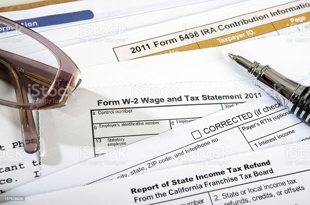 Tax forms with pen and glasses on top stock photo