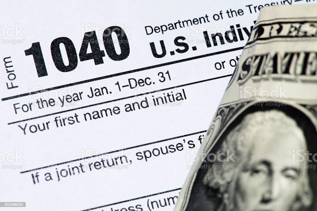 IRS Tax Return Form 1040 and dollar bill stock photo