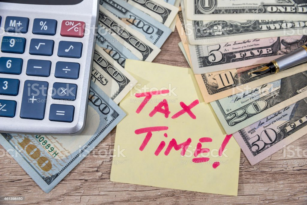 tax tax time with calculator and money on desk. stock photo