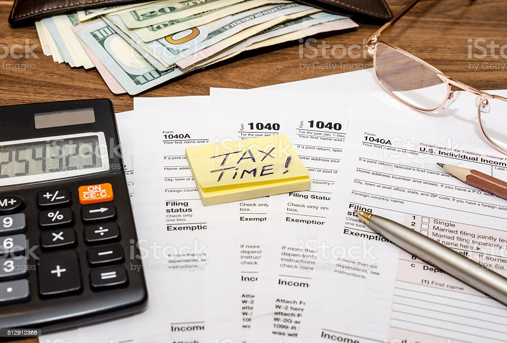 Tax time concept with 1040 tax document and money stock photo
