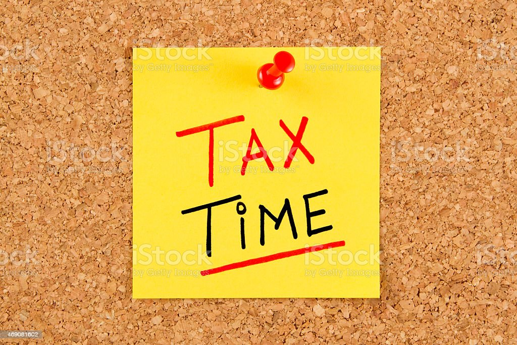 Tax Time Note Pinned on Bulletin Board stock photo