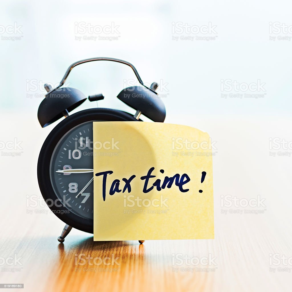 Tax Time sticky note on clock stock photo
