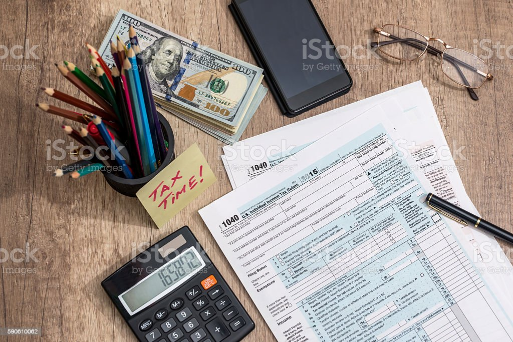 tax time. tax form with money. pen stock photo
