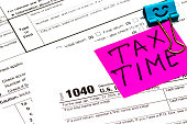 Tax time written on a bright sticker note paper clip