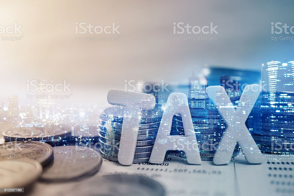 'tax' wooden text and rows of coins stock photo