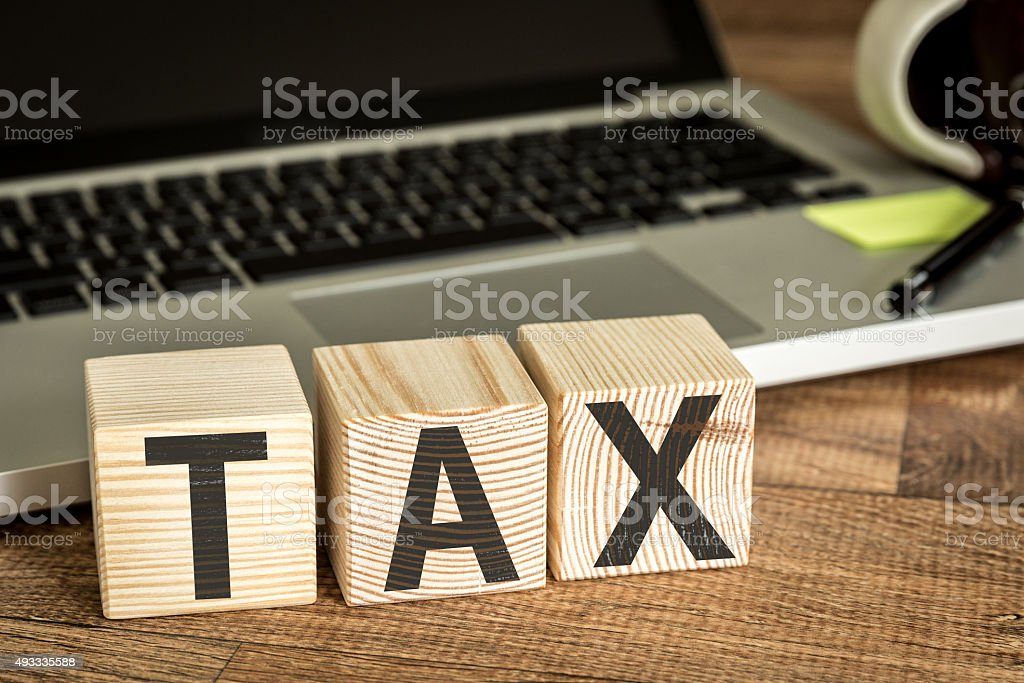 Tax written on a wooden cube stock photo