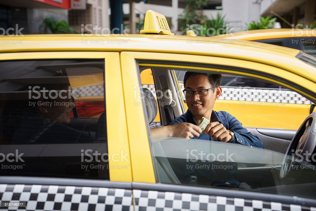 taxi driver driving car happy client paying money stock photo