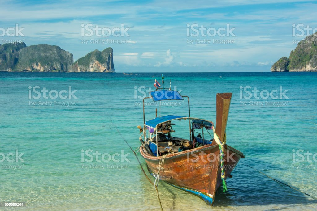 Taxi long-tail boat docked on the tropic beach stock photo