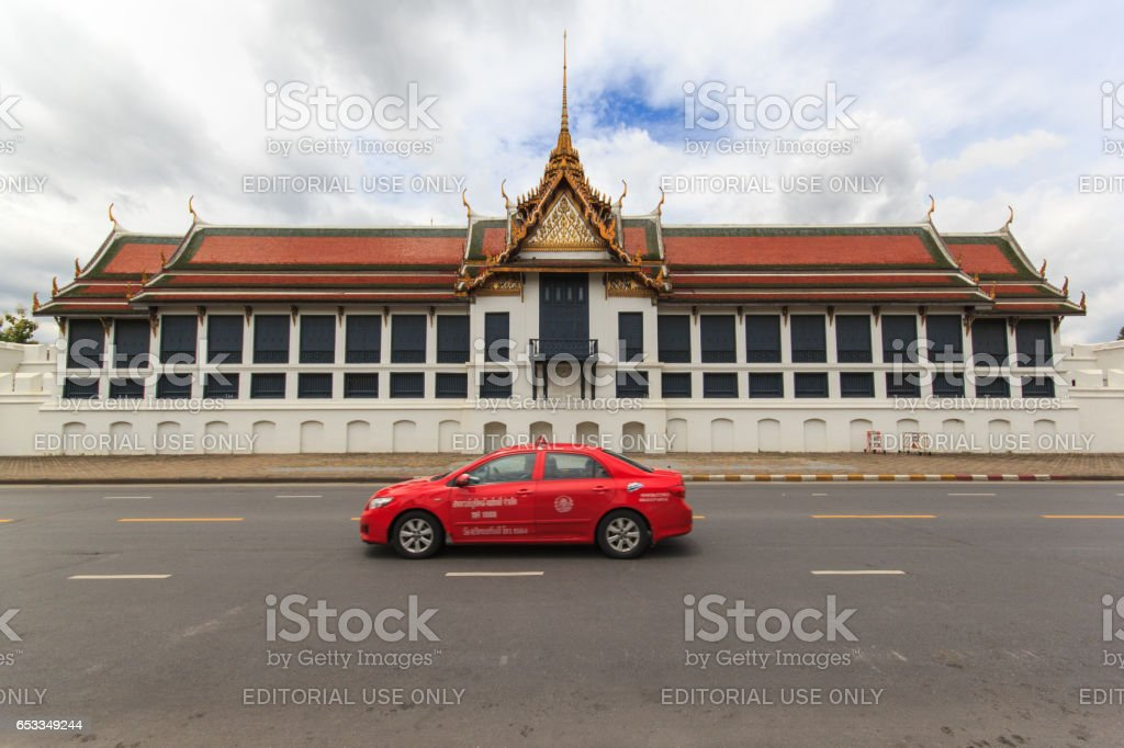 BANGKOK, THAILAND - SEBTEMBER 21, 2013: Taxi on the road in front of the famous Buddhist Temple Wat Phra Kaew, one of the main landmarks of Bangkok, Thailand stock photo