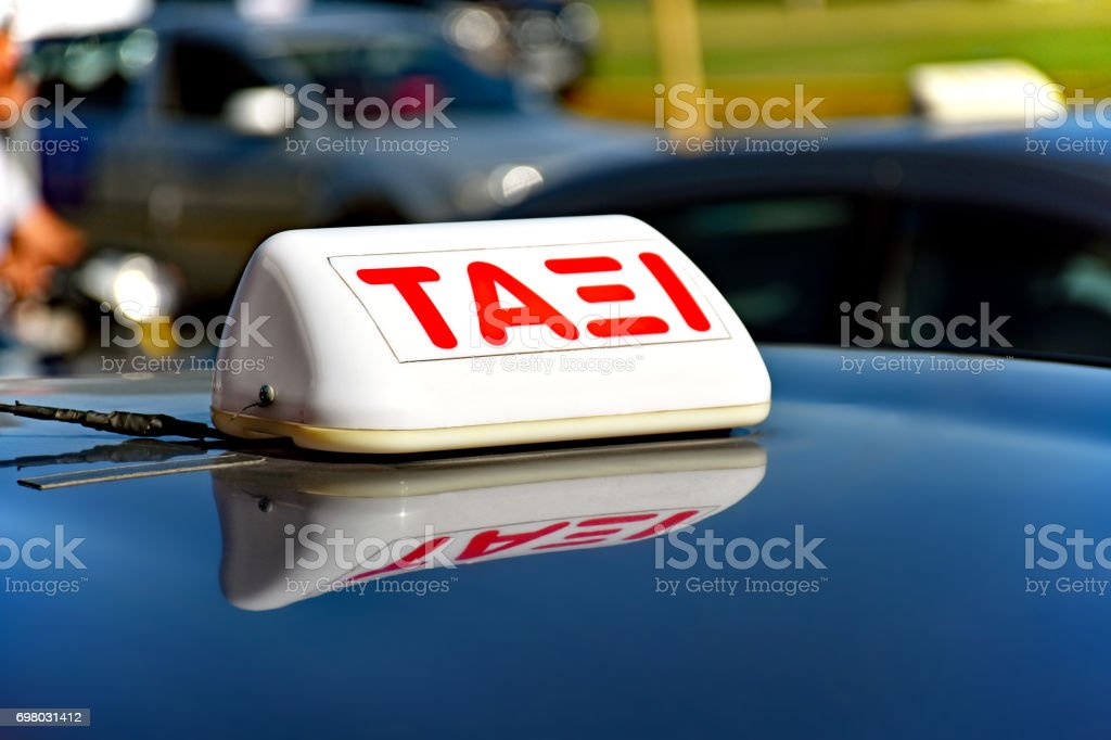 Taxi sign in Greek language on the shiny roof of a car stock photo