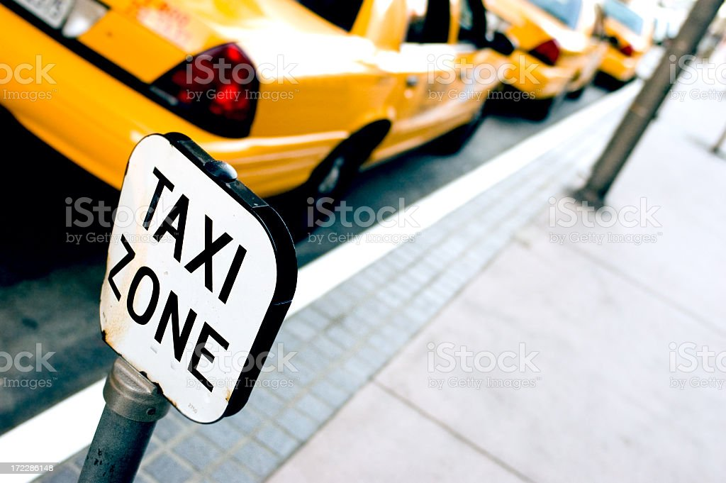 A taxi zone sign on the sidewalk by a line of taxis royalty-free stock photo