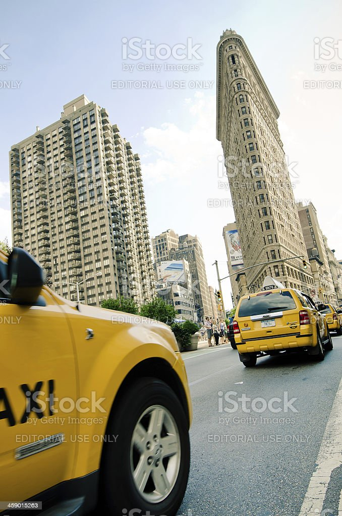 Taxis along 5th Avenue with Flatiron Building in Manhattan royalty-free stock photo