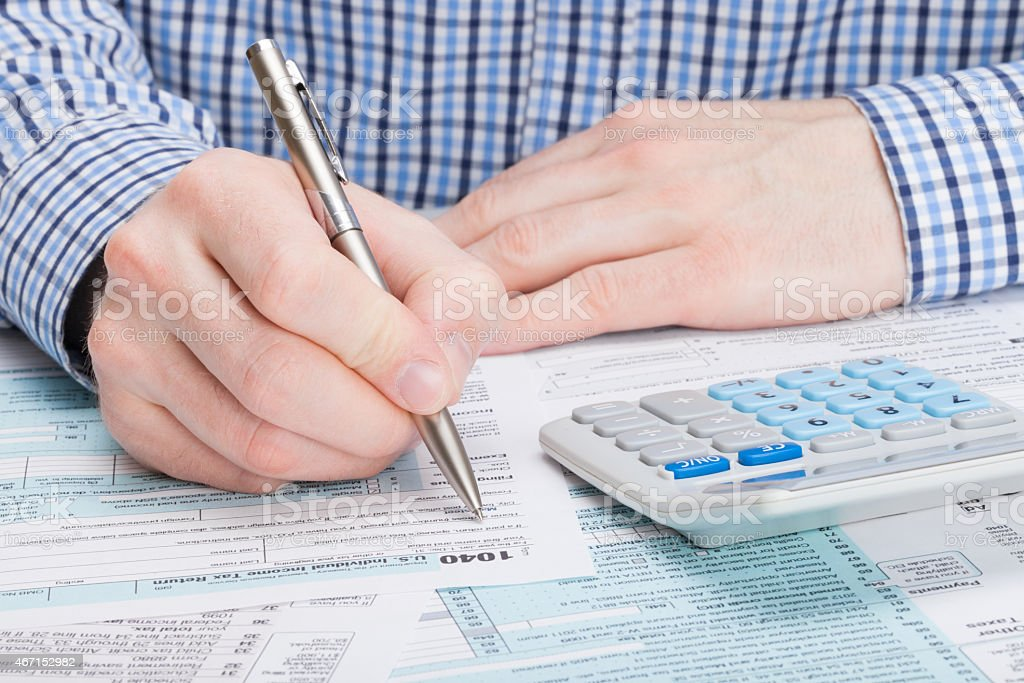 Taxpayer filling out 1040 Tax Form stock photo