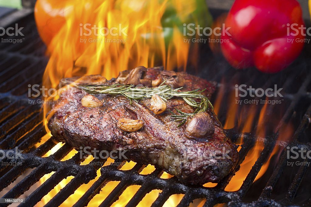T-Bone Steak and Bell Peppers on Grill with Flames royalty-free stock photo
