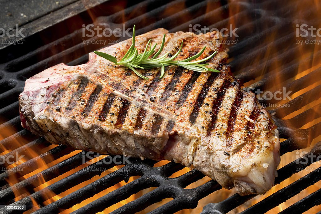 T-Bone Steak on Grill with Flames royalty-free stock photo