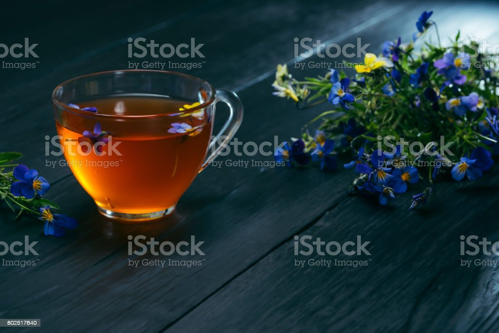 Tea and pancies over black stock photo