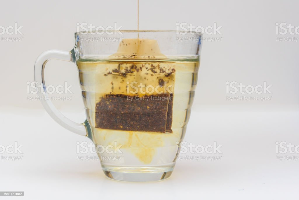 tea bag dipping into glass of hot water stock photo