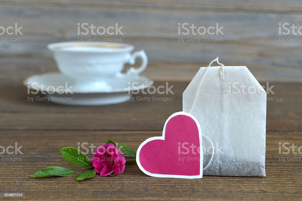 Tea bag with heart-shaped tag, porcelain tea cup and rose stock photo