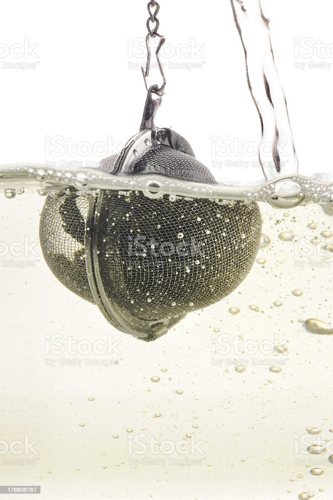Tea ball with hanging into hot water royalty-free stock photo