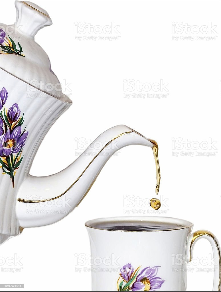 Tea being poured into a cup from a matching teapot royalty-free stock photo