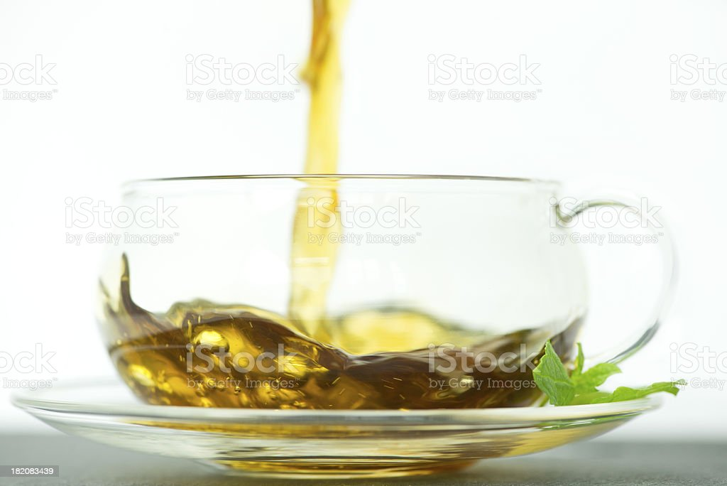 tea being poured into a glass teacup stock photo