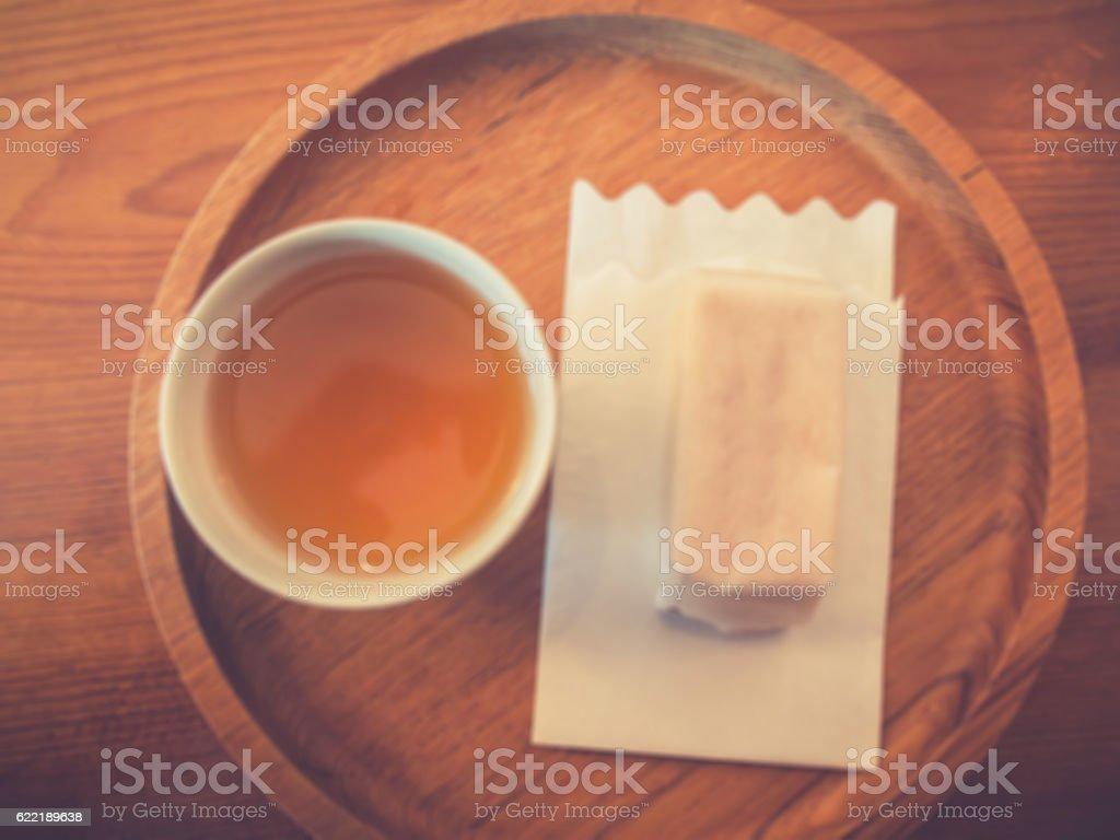 Tea, cake and napkin on wooden plate stock photo