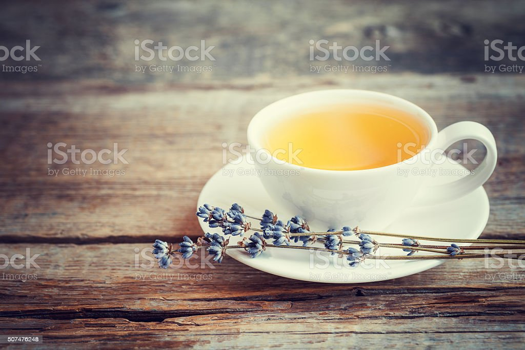 Tea cup and dry lavender flowers on table. Selective focus. stock photo