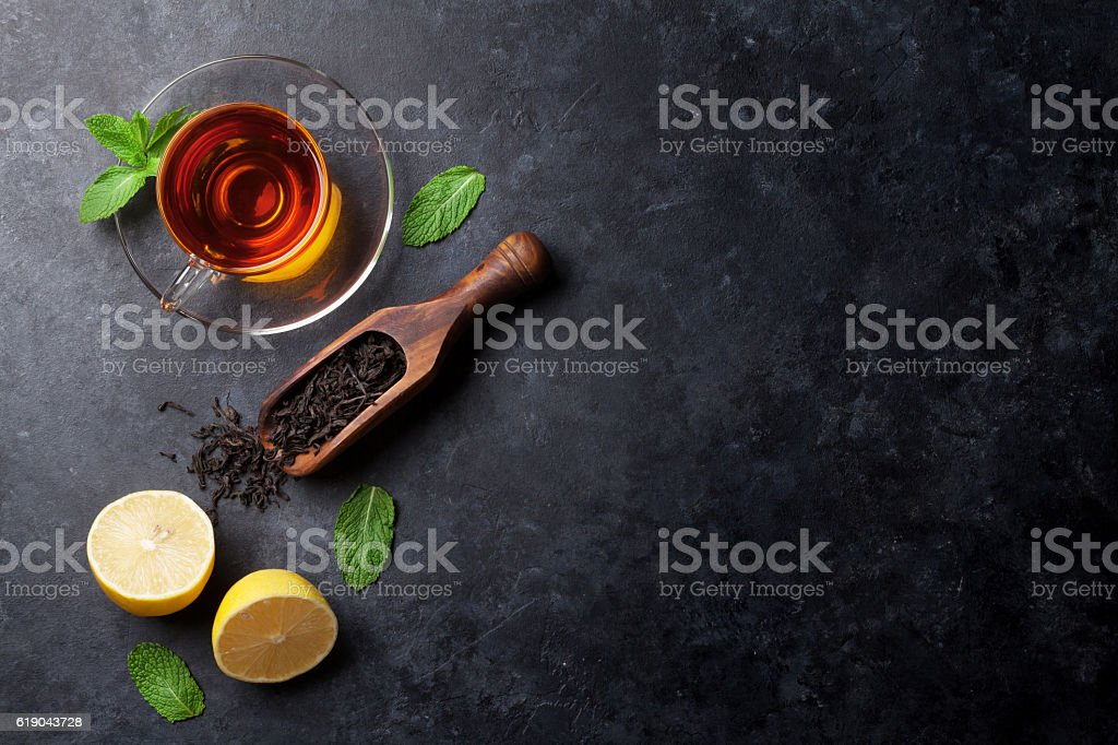 Tea cup and dry tea in spoon stock photo