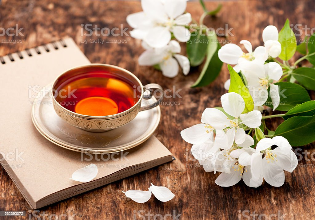 Tea cup, notebook and white spring flowers stock photo