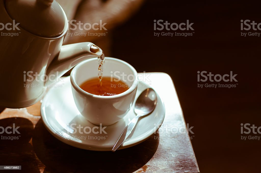 Tea cup on saucer, with tea being poured, stock photo