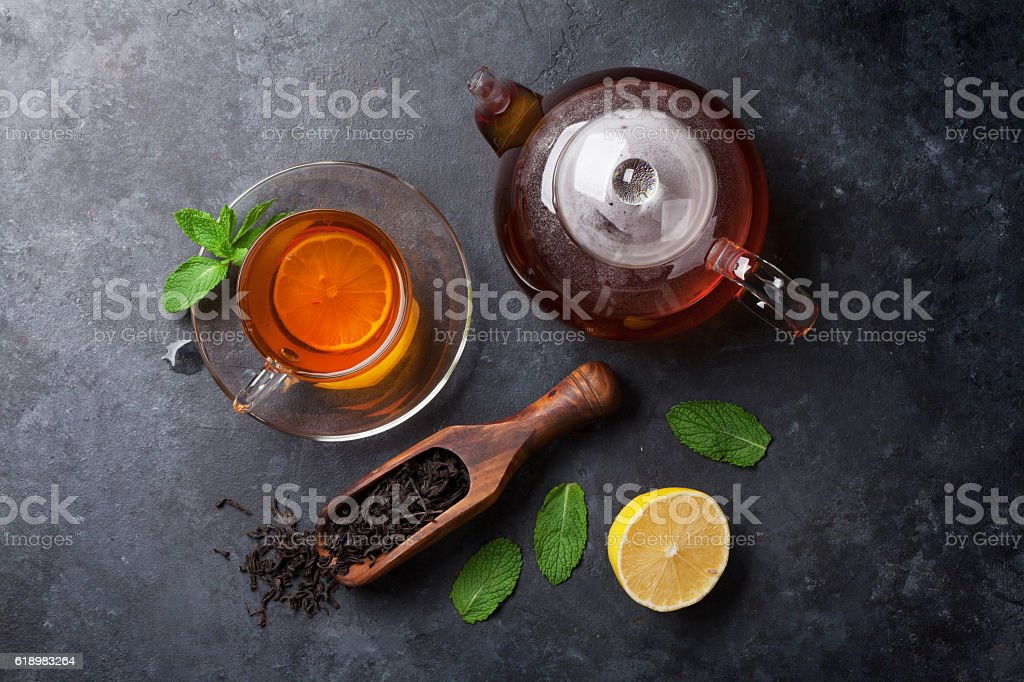 Tea cup, teapot and dry tea in spoon stock photo