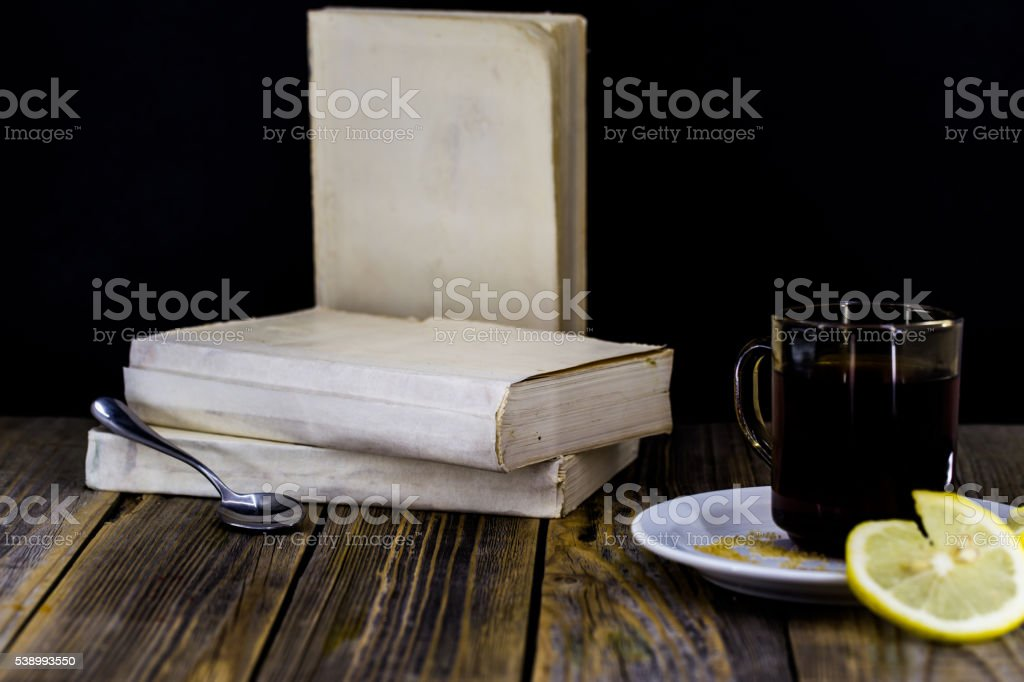 tea Cup with lemon, wooden background, books stock photo