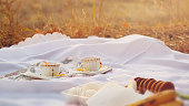 Tea cups outdoors at picnic during autumn with bokeh and