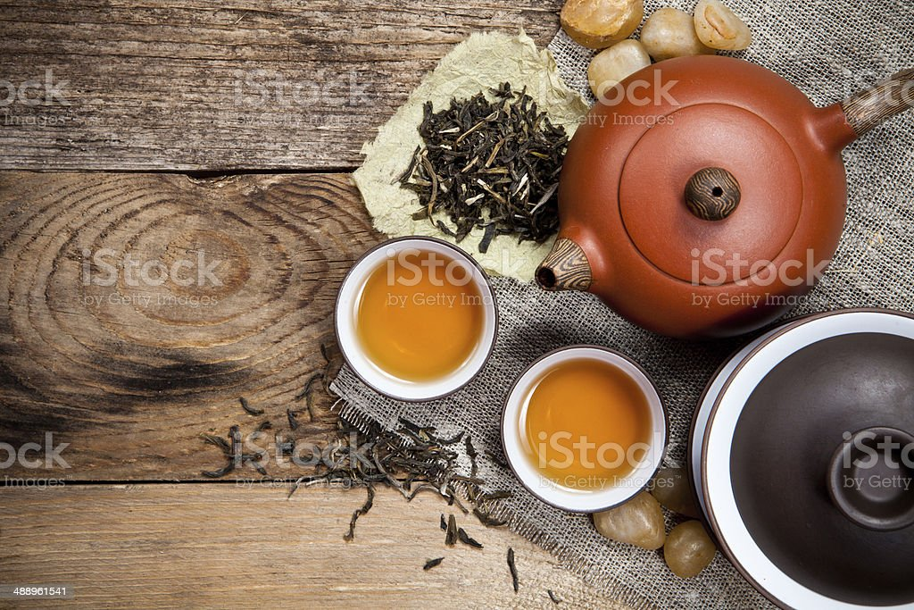 Tea cups with teapot on table stock photo