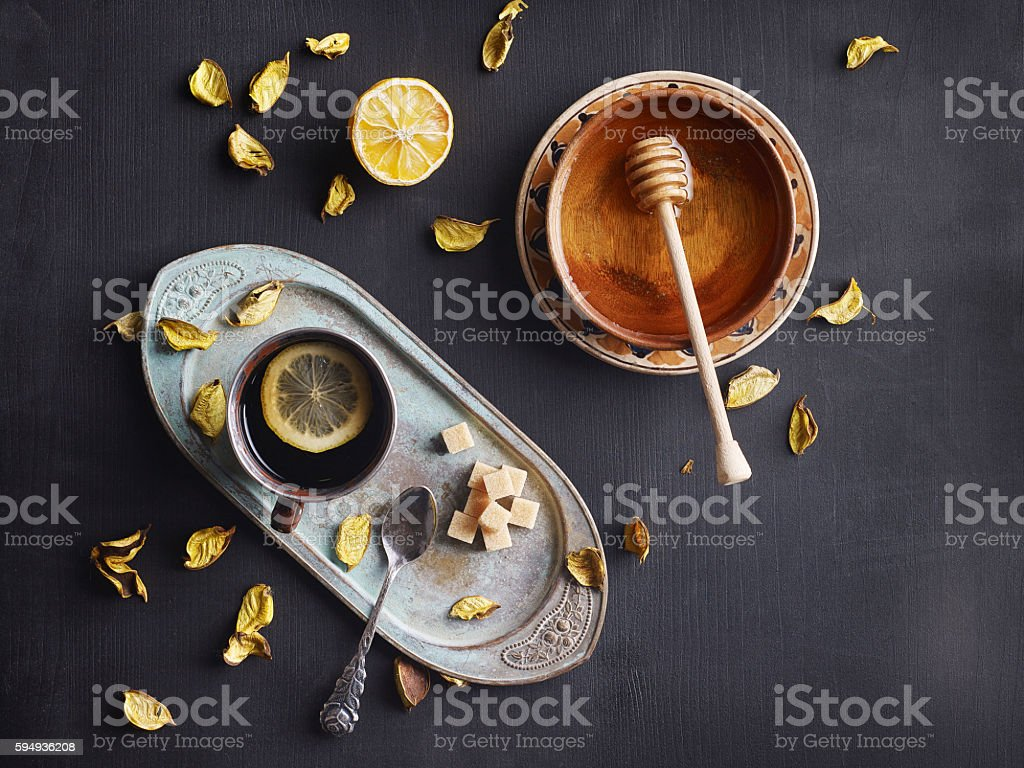 Tea, honey and dried herbs on black background. stock photo