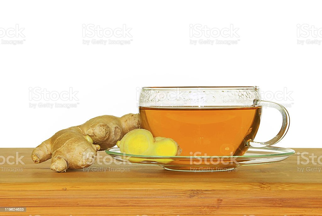 Tea in a transparent cup with ginger on the side stock photo